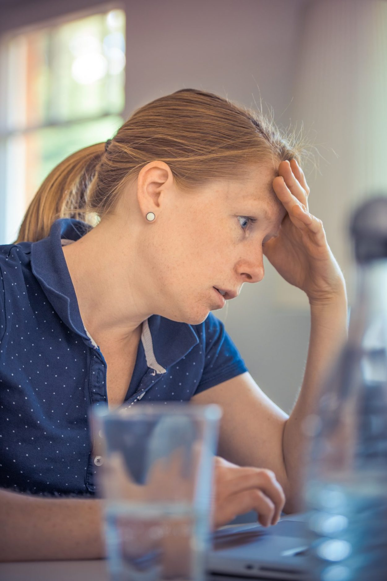 Woman with hand on forehead in frustration from imposter syndrome. She's wearing a blue polo with white polka dots.