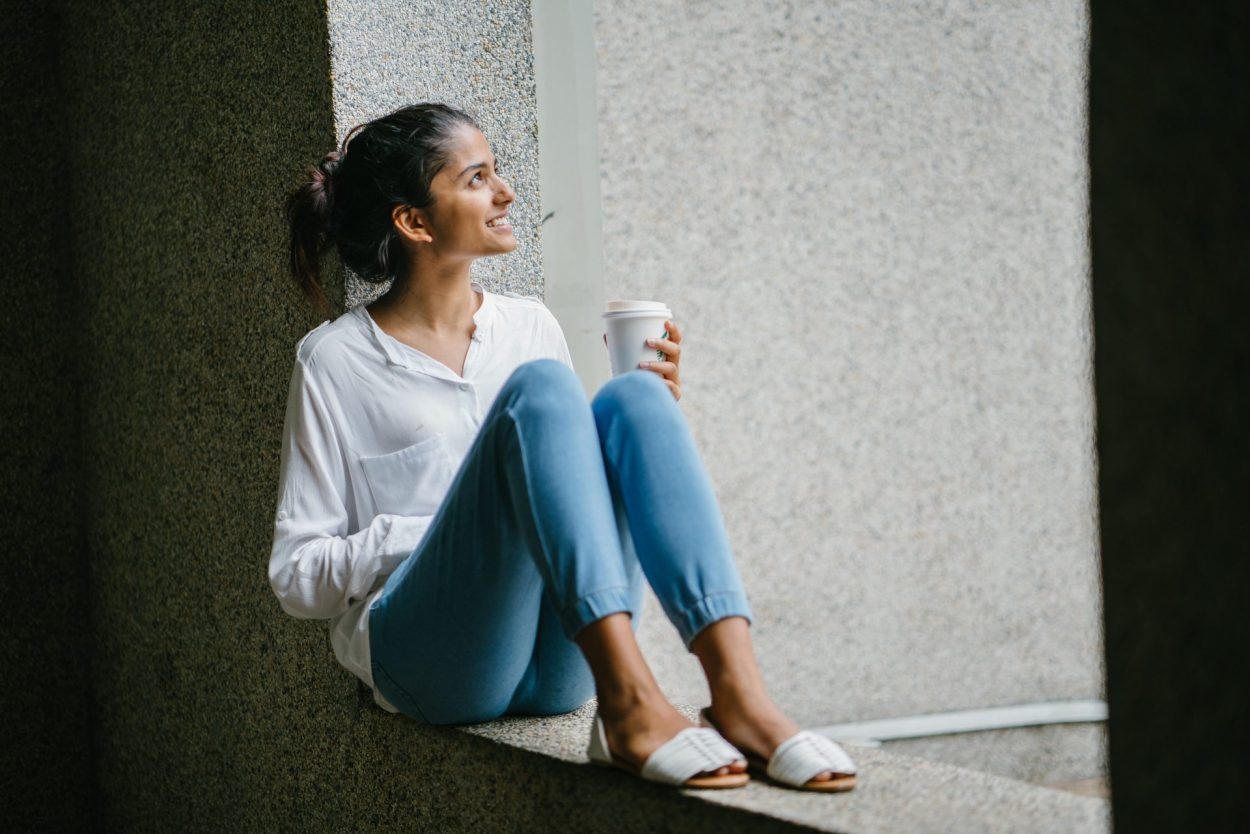 Womnan with coffee cup looking up in hope to break the cycle of imposter syndrome
