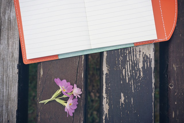 Opened notebook on a wooden table outdoors