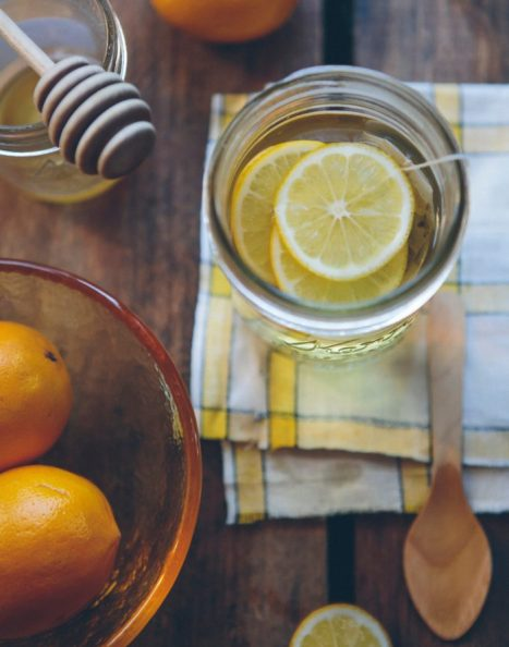 Glass of lemon water with honey and citrus fruit bowl