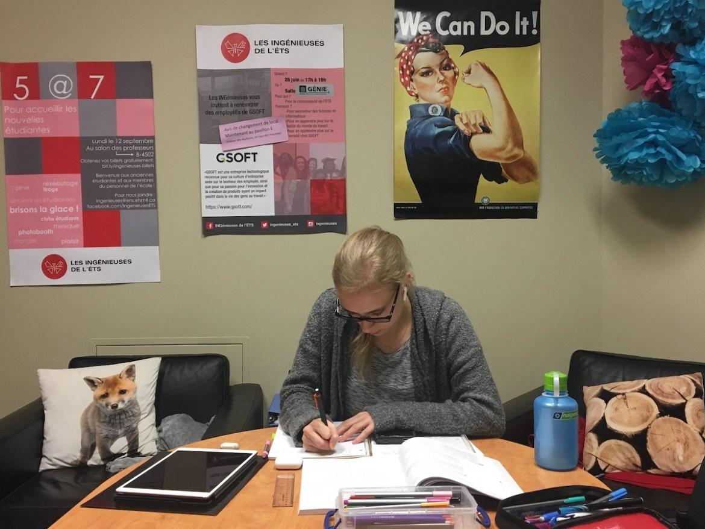 Marie qui étudie à une table avec des affiches en arrière-plan