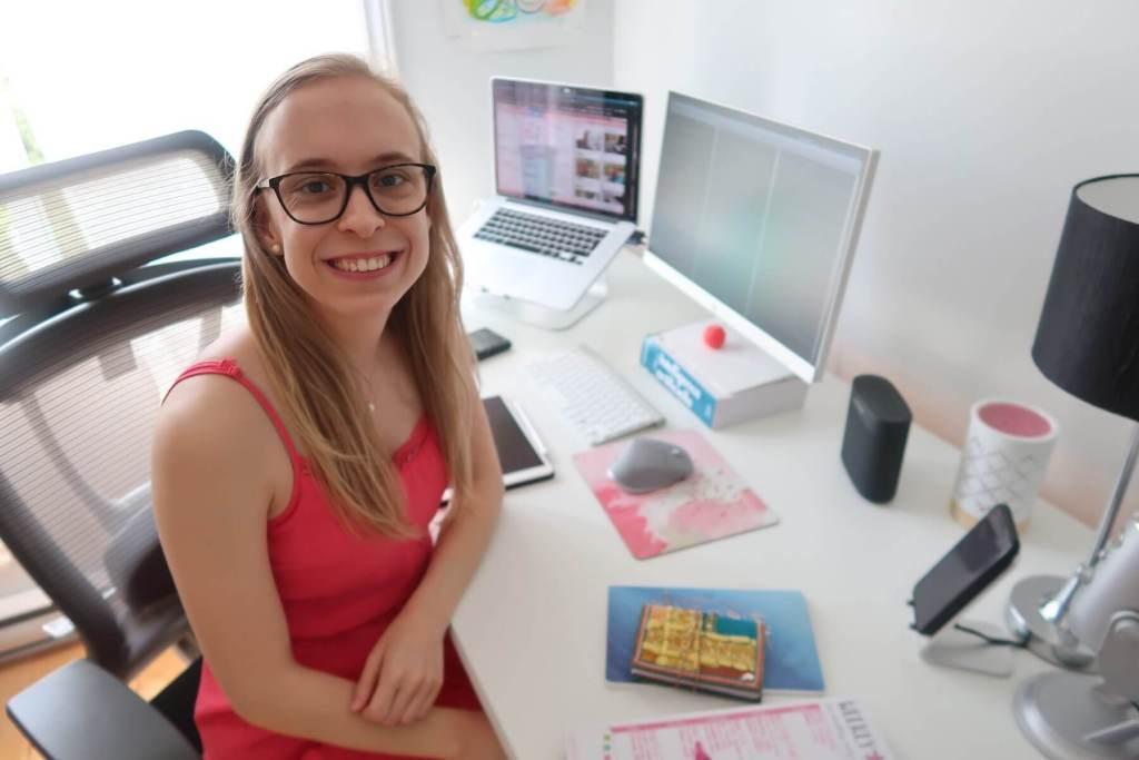 Marie-Philippe souriant à la caméra devant son bureau de travail avec son ordinateur