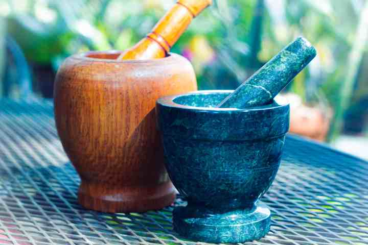 two mortar and pestles.  A green stone mortar and pestle placed slightly in front of a slightly larger mortar and pestle made out of wood.