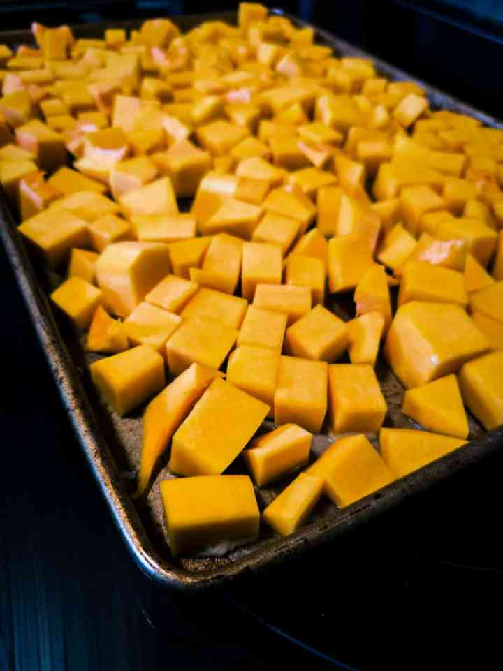 A cookie sheet with raw cubed butternut squash ready to be placed in the oven for roasting