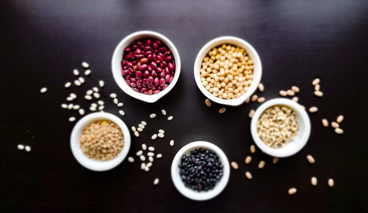 tabletop with an assortment of beans.  Clockwise in bowls; garbanzos, black-eyed peas, black beans, lentils, red beans.  Scattered on table, left white beans; right pinto beans.