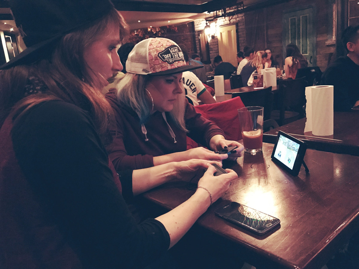 Leah & Cat play Mario Kart 8 Deluxe in a bar on the Nintendo Switch. Photo by Girls on Games