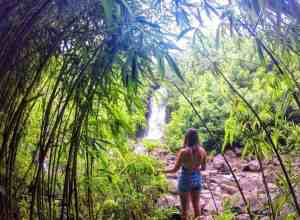 Girls Who Travel | Featured Member Ruthie poses with a waterfall in a lush forest.