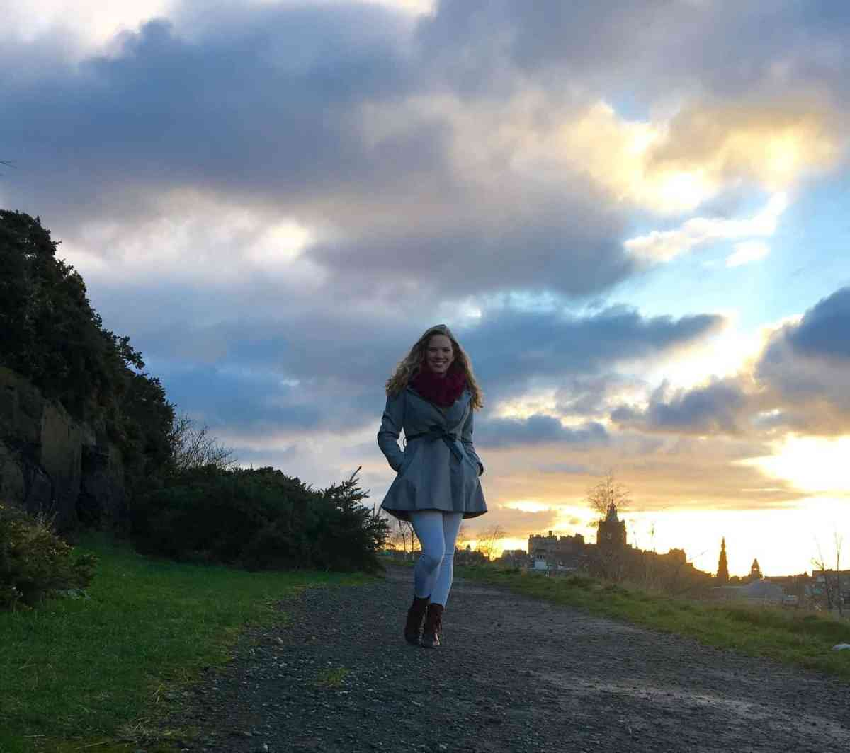 Girls Who Travel   Author Shelby poses in Scotland. A cloudy, yet bright, sky and the Edinburgh skyline are in the background