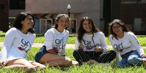 4 girls wearing teen advisers shirt sitting on the grass floor and laughing on the picture
