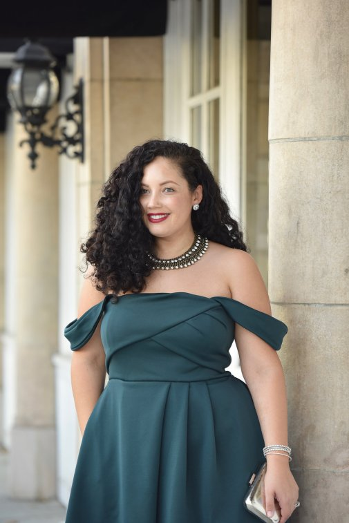 Girl With Curves blogger Tanesha Awasthi wears an emerald off-shoulder dress and statement necklace in downtown San Jose, CA.