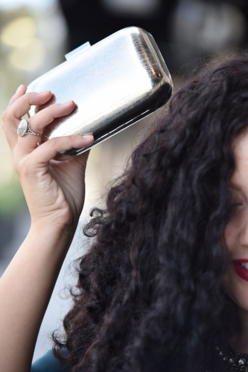 Girl With Curves blogger Tanesha Awasthi holding a silver box clutch.