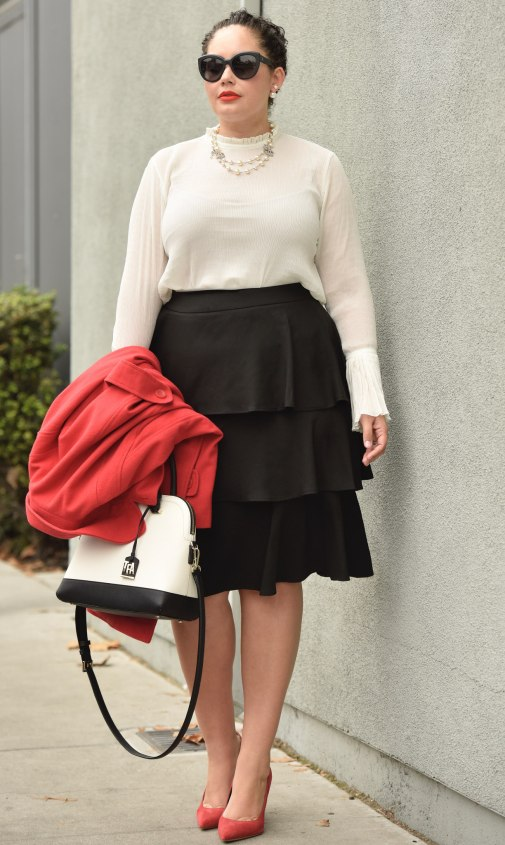 Girl With Curves blogger Tanesha Awasthi wears a plus size ruffle skirt, bell sleeve blouse, red swing coat, kate spade bag, Chanel sunglasses and Chanel necklace and red pumps.