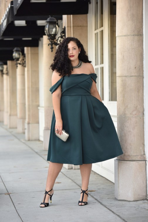 Girl With Curves blogger Tanesha Awasthi wears an emerald off-shoulder dress, silver box clutch, statement necklace and t-strap heels in downtown San Jose, CA.