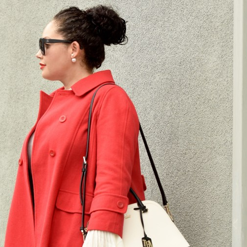 Girl With Curves blogger Tanesha Awasthi wears a bell sleeve blouse, red swing coat, kate spade bag, double pearl earrings and Chanel sunglasses