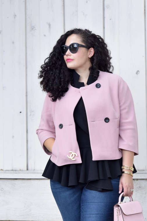 Girl With Curves blogger Tanesha Awasthi wears a pink cropped jacket, peplum top, skinny jeans.
