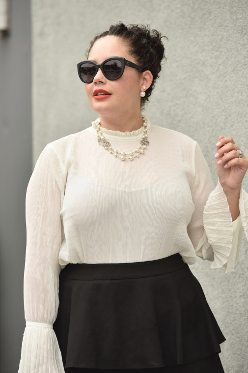 Girl With Curves blogger Tanesha Awasthi wears a plus size ruffle skirt, bell sleeve blouse, Chanel sunglasses and Chanel necklace.
