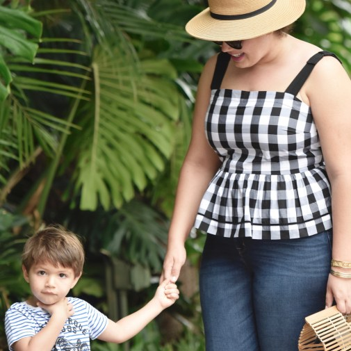 Girl With Curves blogger Tanesha Awasthi wears a gingham peplum and boater hat in Hawaii with her son, Narayan Awasthi.