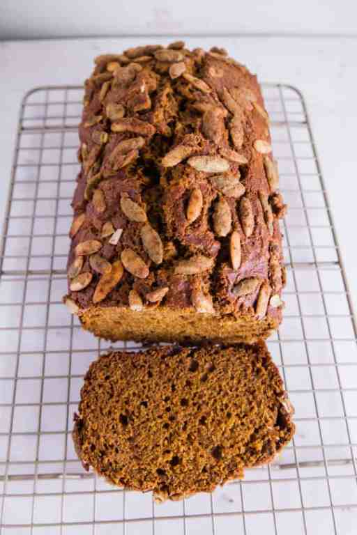 Pumpkin bread with pumpkin spice seeds on a cooling rack