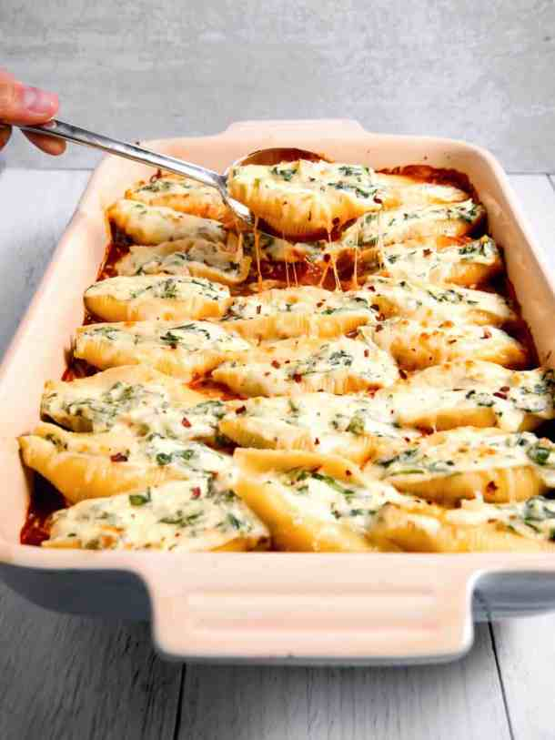 spinach and cheese stuffed shells in red sauce with a cheese pull