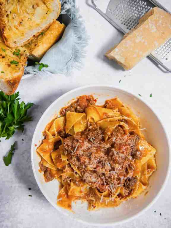 flaylay of a bowl of bolognese over pappardelle pasta with garlic bread and parmesan block in background