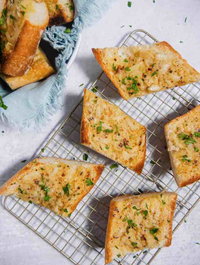 slices of garlic bread on a baking rack with a bowl of more garlic bread in the corner