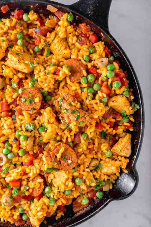 Chicken and chorizo paella in a cast iron skillet with yellow rice and vegetables