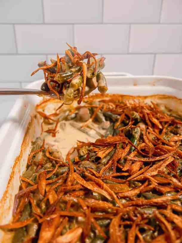 Spoon scooping out green bean casserole with fried shallots on top