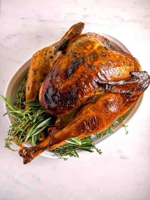overhead photo of a roasted turkey with crispy brown skin and herbs surrounding