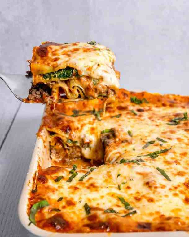 spinach and beef lasagna being lifted out of rectangular baking dish