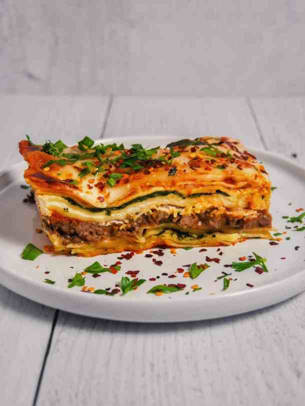 layers of spinach and beef lasagna with cheese and bechamel sauce