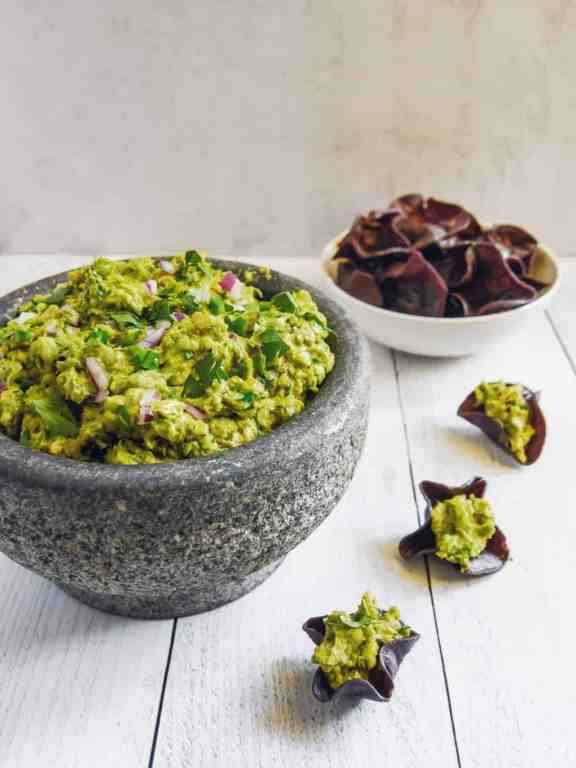 Front shot of guacamole in a stone bowl with a bowl of blue corn tortilla chips in background and small chips with guacamole inside