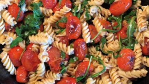blistered tomatoes and pasta in cast iron skillet