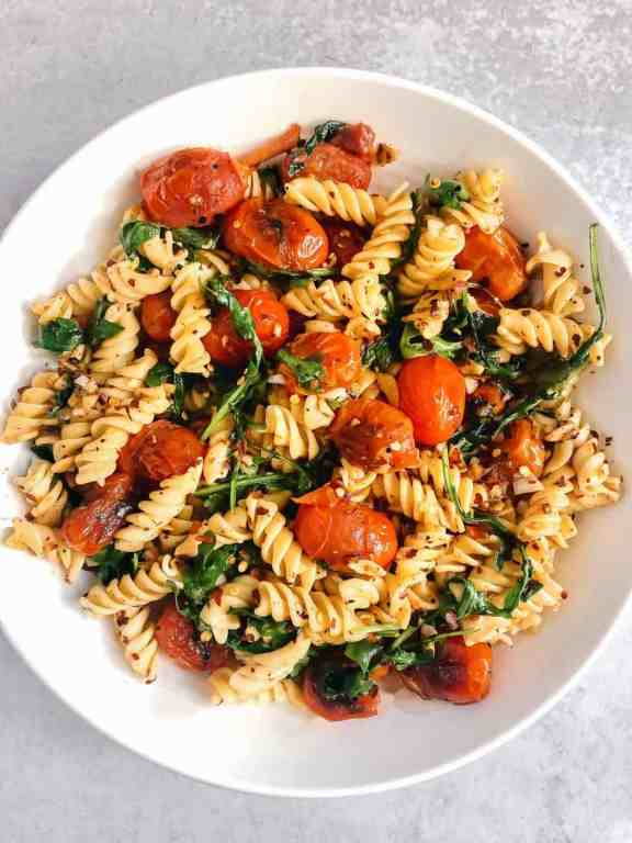 Blistered tomato pasta with fresh arugula, garlic, and gluten free pasta