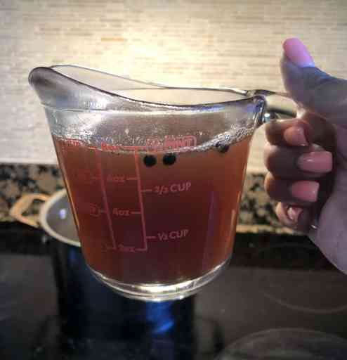 holding a glass pyrex measuring cup with 1 cup of pickling liquid inside