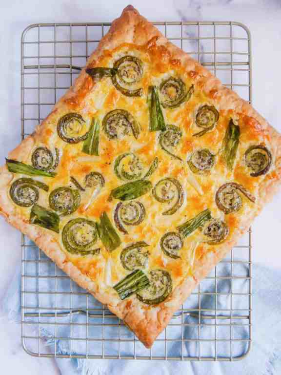 overhead shot of cooked puff pastry cheese tart with roasted fiddlehead ferns and ramps on a metal rack