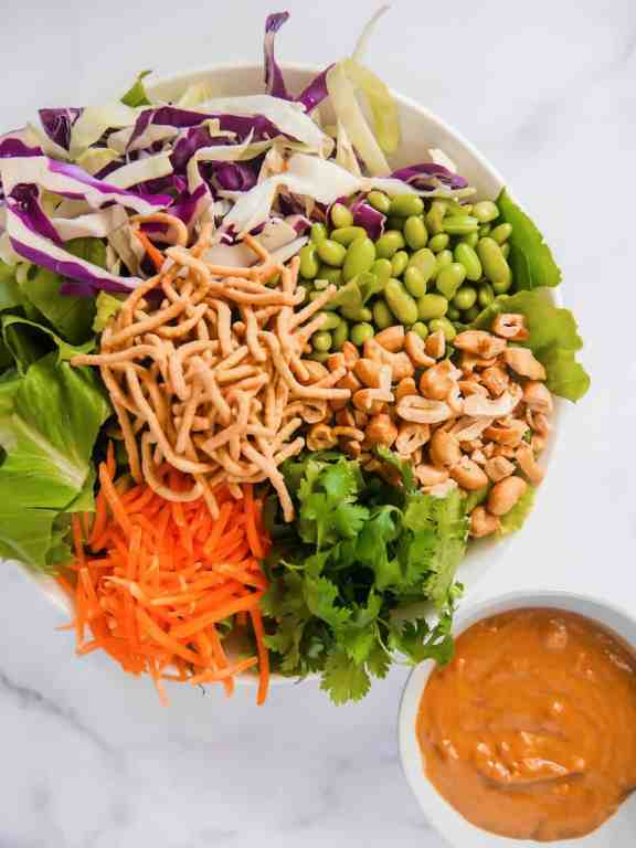 overhead shot of deconstructed asian salad in a bowl with cashews, edamame beans, sliced carrots, lettuce, cabbage, cilantro, crunchy noodles, and a small bowl of peanut dressing on side