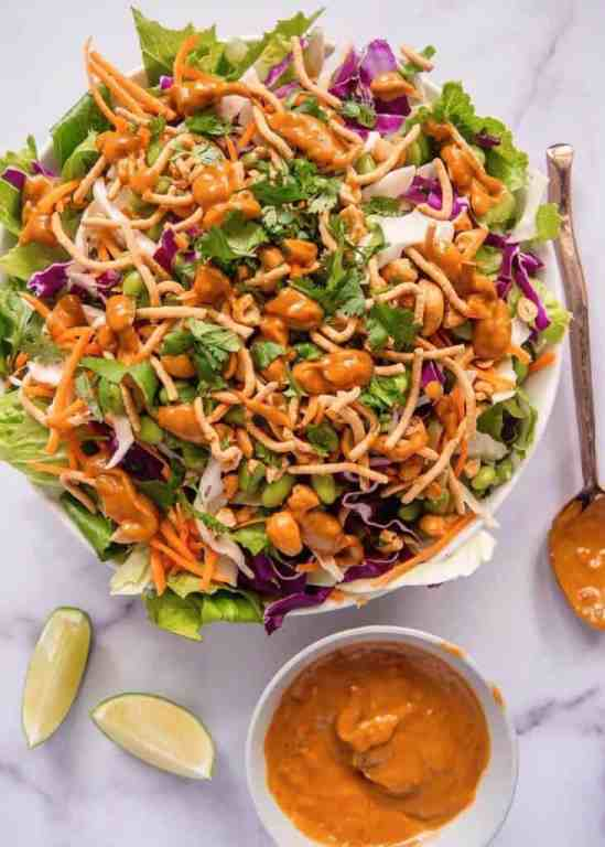 overhead shot of mixed asian salad in a bowl with spicy peanut dressing dribbled over the top of the salad, with spoon dipped in peanut dressing, and two limes