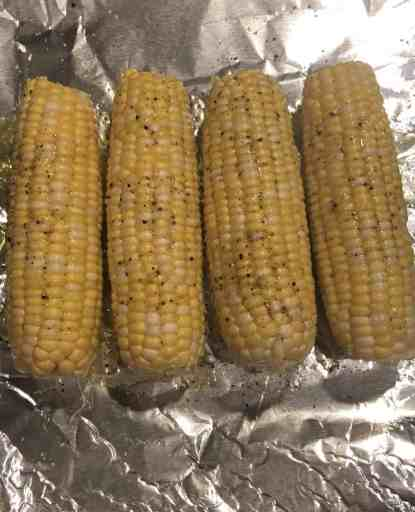 uncooked shucked yellow ears of corn on foil with salt and pepper and olive oil