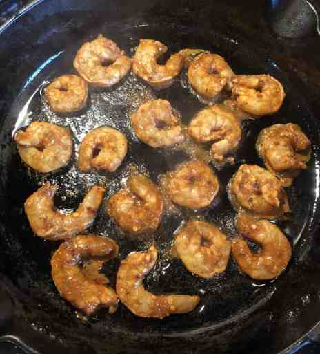 overhead picture of marinated spicy shrimps cooking in a cast iron skillet