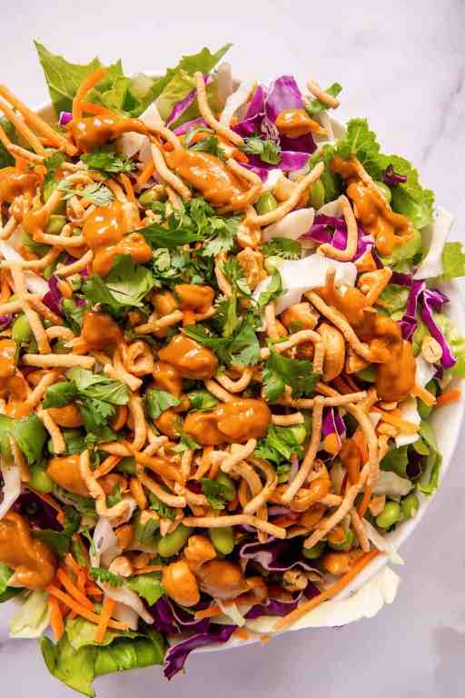 overhead shot of mixed asian salad in a bowl with spicy peanut dressing dribbled over the top
