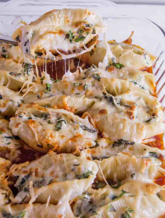 baking dish with cheesy stuffed shells and a spoon pulling one out with cheese stretching