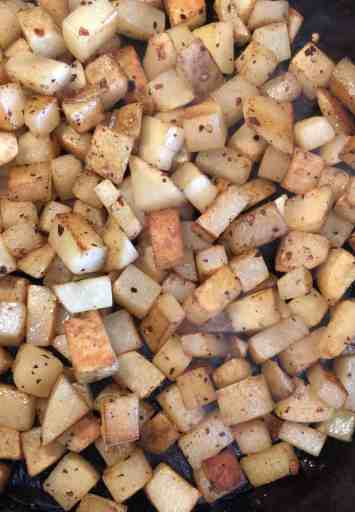 seasoned diced potatoes in a cast iron skillet cooking