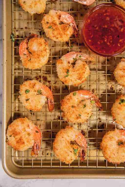 overhead shot of baked coconut shrimps on a baking rack