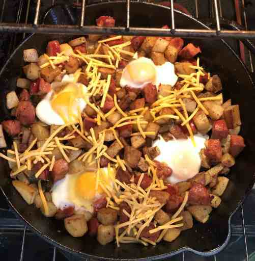 cast iron skillet in the oven with potatoes, chorizo, half cooked eggs, and shredded cheddar cheese on top