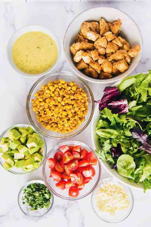 Overhead of individual bowls of the mexican garden chicken ingredients: lettuce, corn, chicken, avocado, tomatoes, and citrus vinaigrette