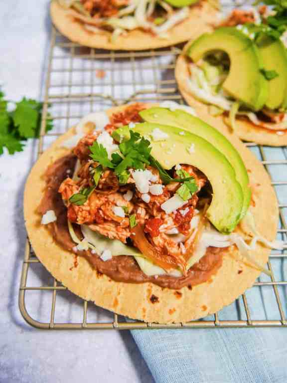 Close up of chicken tinga tacos with refried beans, shredded chicken, avocado, on a baking rack