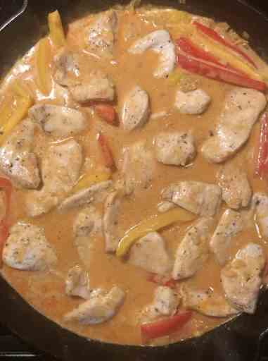 cast iron skillet with red coconut curry chicken broth and pieces of chicken and red bell peppers