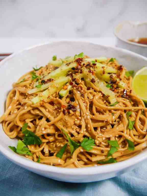 close up photo of sesame noodles in a bowl with szechuan chili oil, cucumber, and fresh cilantro over the top.