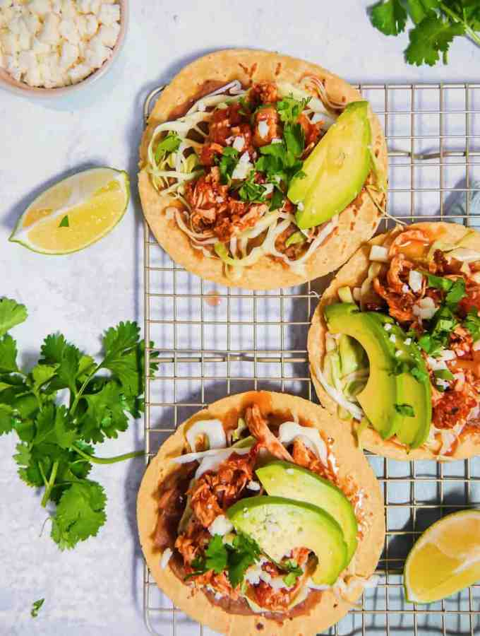 overhead shot of slow cooker chicken tinga tacos with limes, cilantro, and surrounding