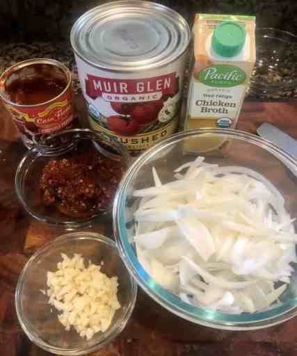ingredients for chicken tinga on a cutting board